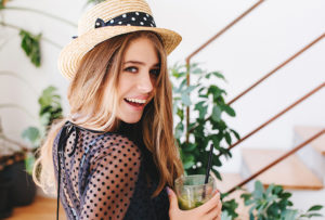 Inspired young woman with long shiny hair looking over shoulder and laughing holding glass of cold beverage. Indoor portrait of happy girl in hat with ribbon drink cocktail with plants on background
