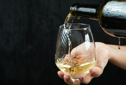 Pouring white wine into the wine glass on dark background