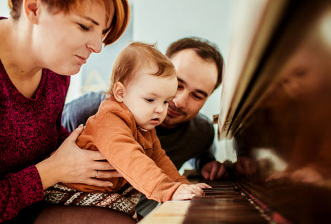 Little girl looks funny playing with mother on the piano