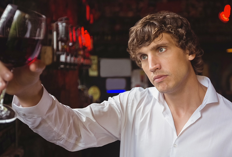 Bartender looking at glass of red wine at bar counter